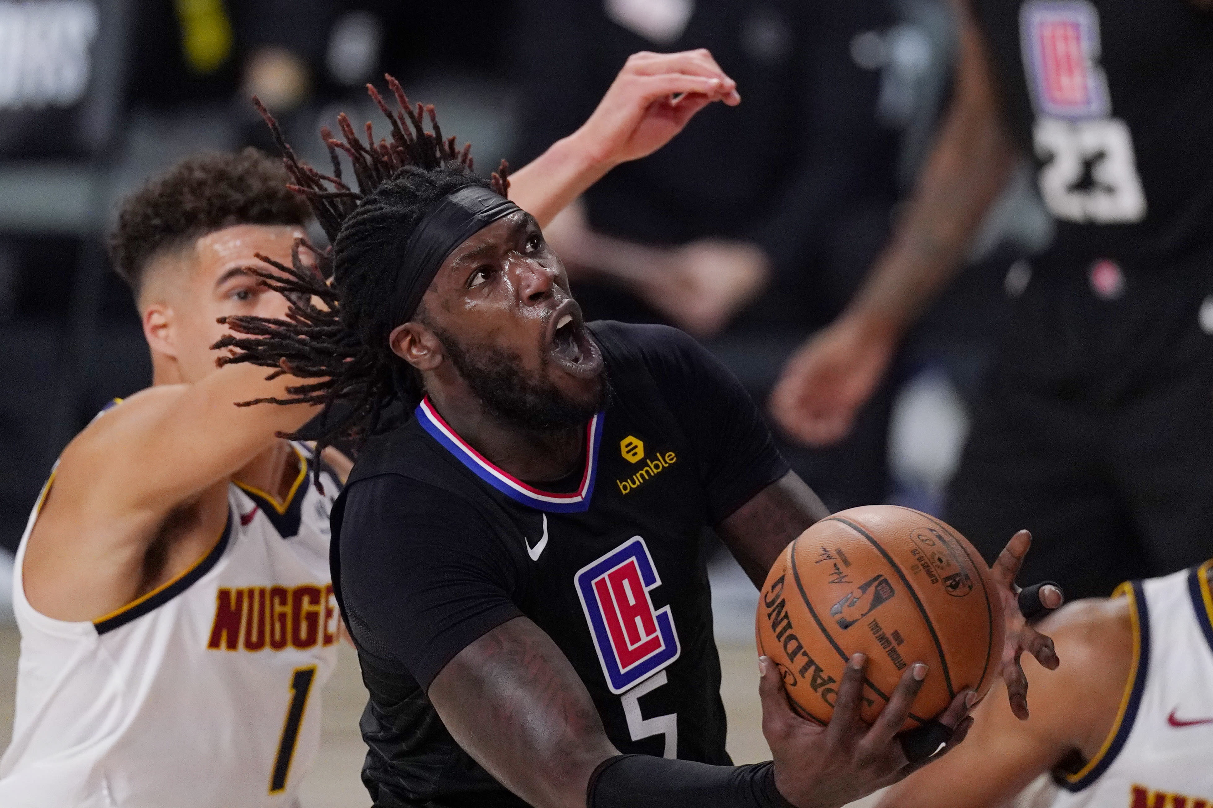 Los Angeles Clippers' Montrezl Harrell (5) drives to the basket past Denver Nuggets' Michael Porter Jr. (1) in the second half of an NBA conference semifinal playoff basketball game Thursday, Sept 3, 2020, in Lake Buena Vista Fla. (AP Photo/Mark J. Terrill)
