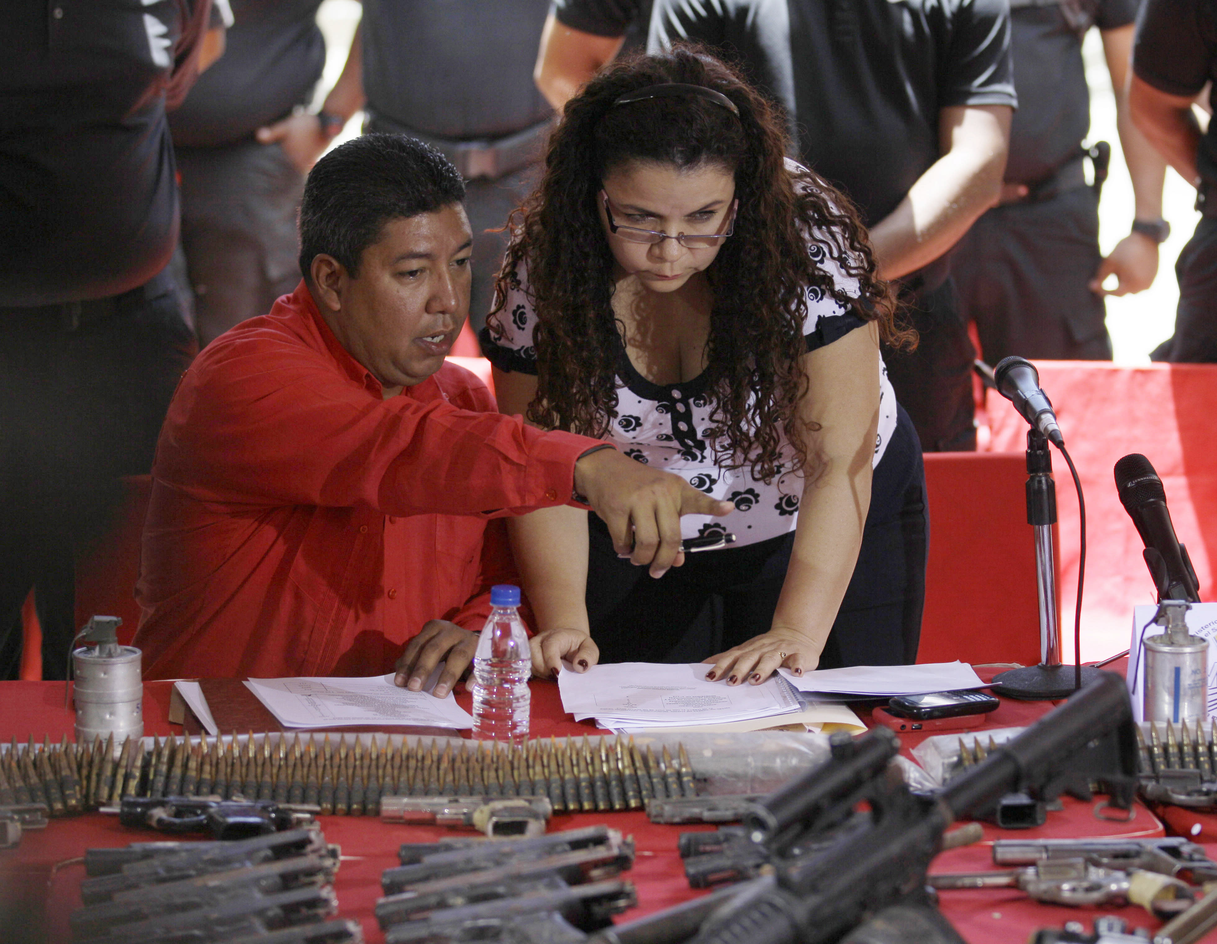 FILE - In this June 3, 2012 file photo, Iris Varela, Venezuela's Minister of Prisons, right, speaks to Wilmer Apostol, Venezuela's Director of Prisons, in front of seized weapons during a news conference at La Planta prison in Caracas, Venezuela. Varela, declared Tuesday, April 23, 2013 that she was preparing a cell for opposition candidate Henrique Capriles for allegedly directing the purported clinic attacks and other violence against government buildings and supporters. (AP Photo/Fernando Llano, File)