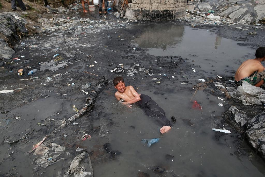 """Iraqis are delighted to be able to dip in the same pool after close to three years trapped in the so-called """"caliphate"""" IS declared (AFP Photo/AHMAD GHARABLI)"""