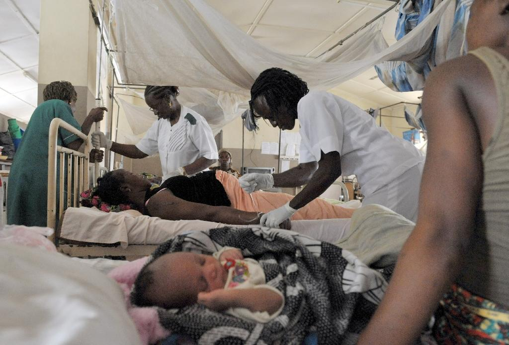 Nurses give aid to a pregnant woman before delivering a baby at the maternity ward of the central hospital in Freetown on September 22, 2009 (AFP Photo/Issouf Sanogo)