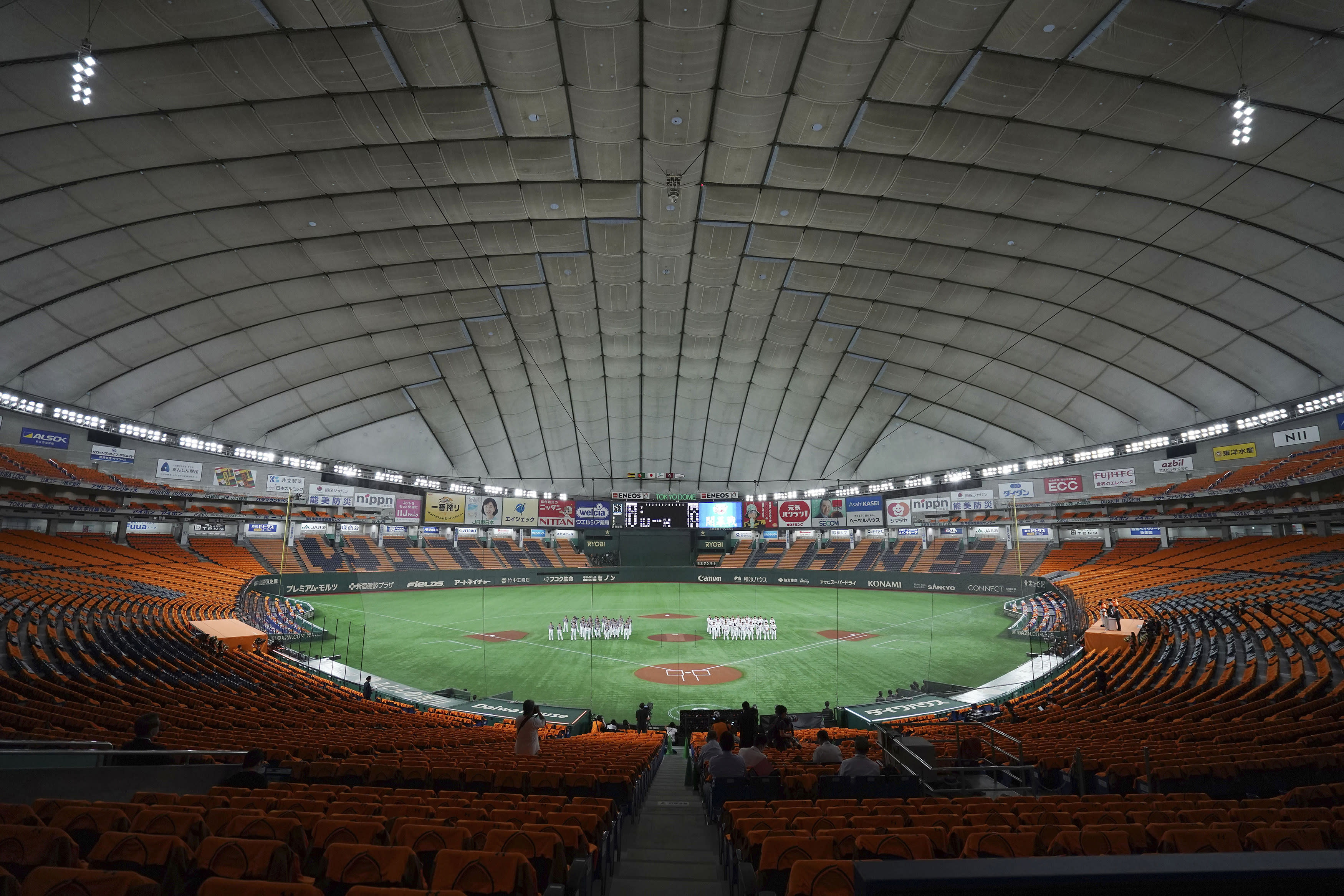 FILE - In this June 19, 2020, file photo, players gather in the empty stands prior to a baseball game between the Yomiuri Giants and the Hanshin Tigers at the Tokyo Dome in Tokyo. Japan's professional baseball and soccer leagues will begin allowing fans this week, the head of both leagues said on Monday, July 6, 2020. (AP Photo/Eugene Hoshiko, File)