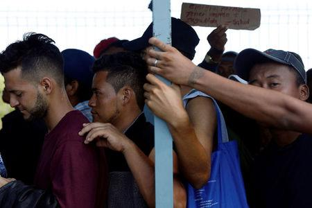 Central American migrants, part of a caravan trying to reach the U.S., line up as they wait to open the gate on the bridge that connects Mexico and Guatemala in Ciudad Hidalgo