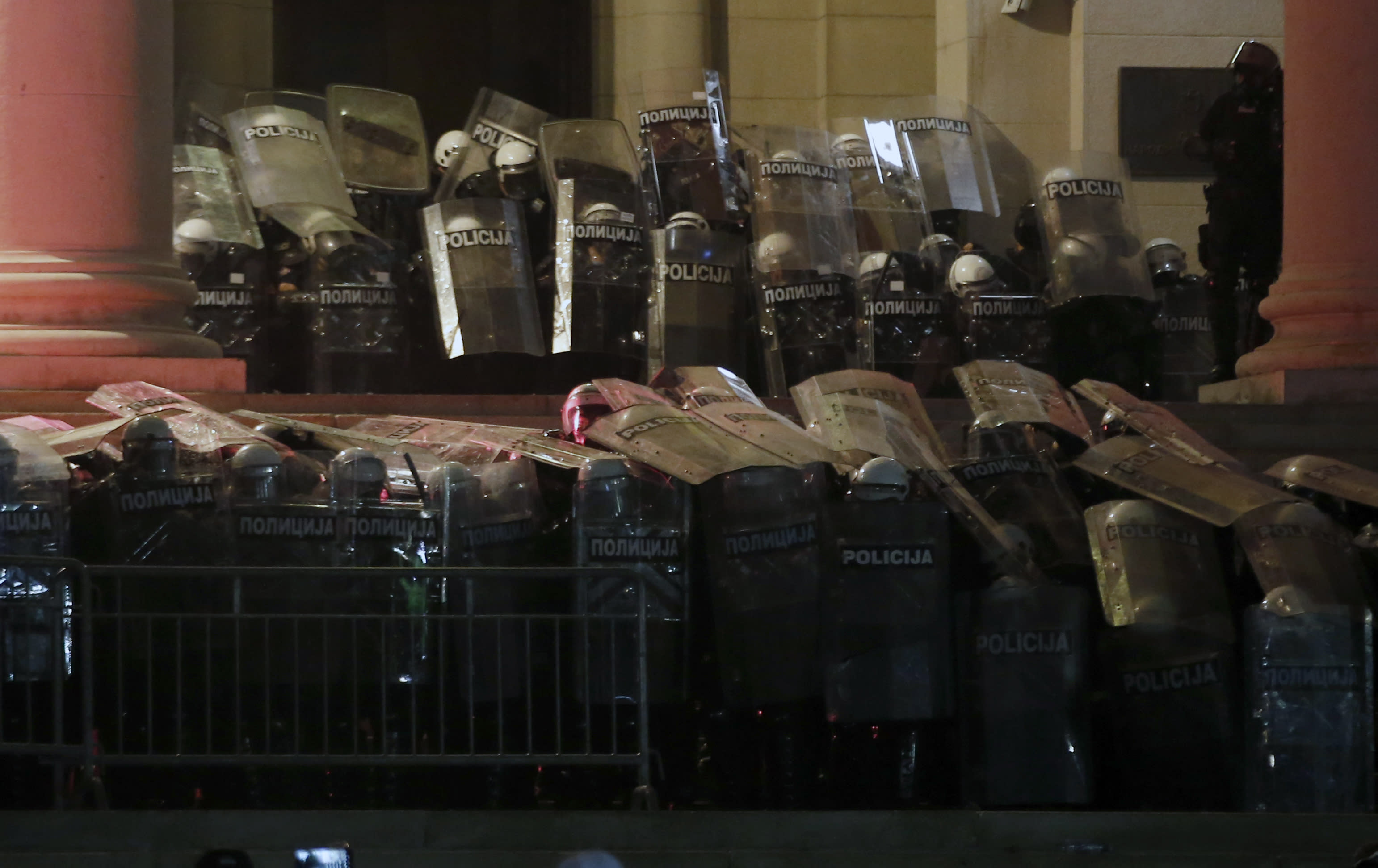 Serbian riot police guard the Serbian parliament building during a protest in Belgrade, Serbia, Friday, July 10 2020. Hundreds of demonstrators tried to storm Serbia's parliament on Friday, clashing with police who fired tear gas during the fourth night of protests against the president's increasingly authoritarian rule. The protests started on Tuesday when President Aleksandar Vucic announced that Belgrade would be placed under a new three-day lockdown following a second wave of confirmed coronavirus infections. (AP Photo/Darko Vojinovic)