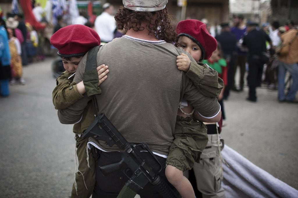 It is already common to see Israeli settlers in West Bank outposts openly carrying rifles, like this one in the settler enclave in central Hebron with his children dressed up in army uniforms for the annual Purim parade (AFP Photo/MENAHEM KAHANA)