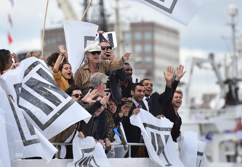 A boat carrying supporters for the Remain in the EU campaign including Sir Bob Geldof (C) shout and wave at Brexit fishing boats as they sail up the River Thames in central London on June 15, 2016 (AFP Photo/Ben Stansall)