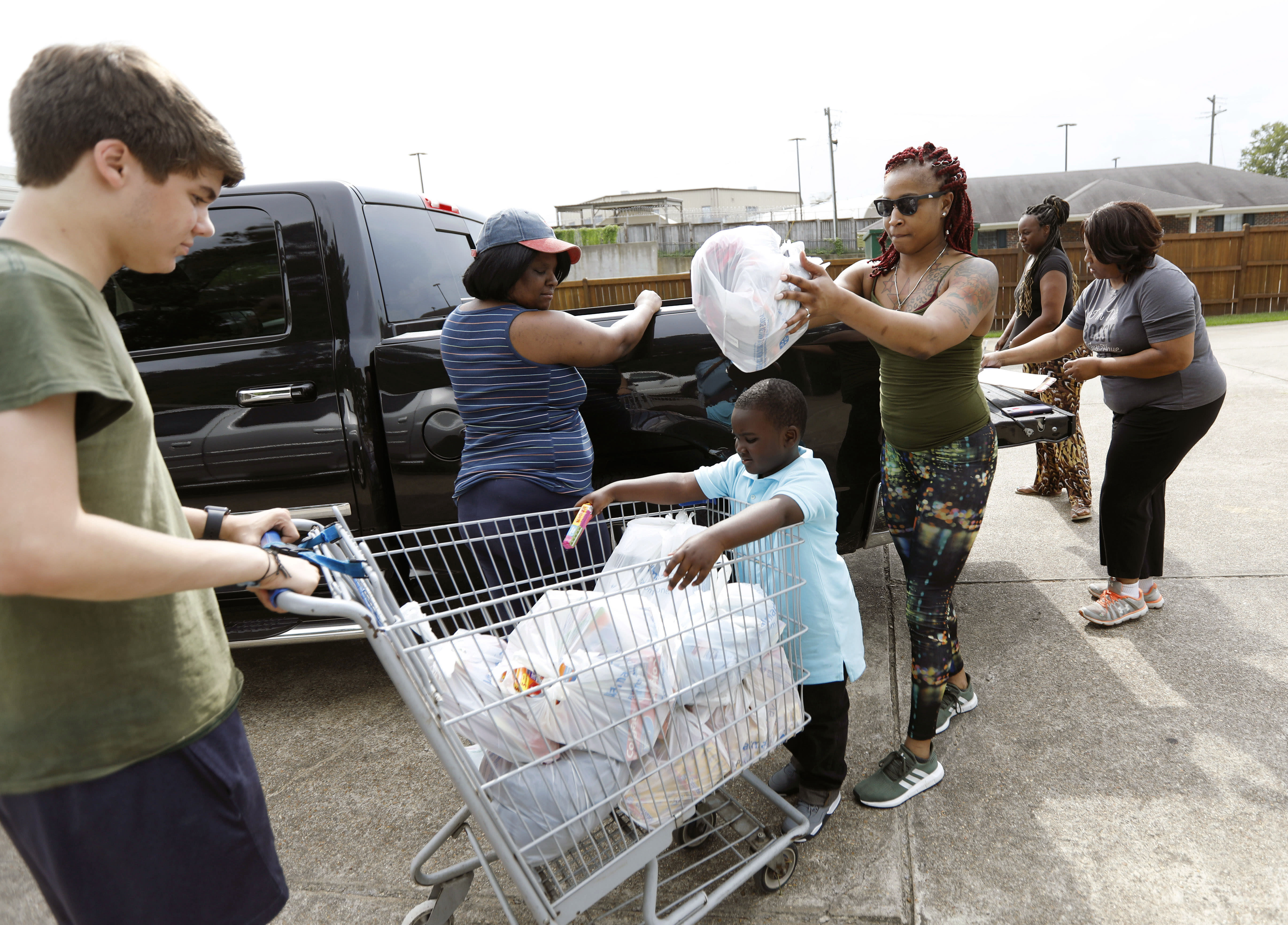 In this Thursday, Aug. 8, 2019 photo, Jesse Van Fleet, left, assists Jasmine Ward and Myles Wright, 5, of Jackson, unload donated items for the pantry at the Carlisle Crisis Center in Forest, Miss. The center, a ministry of Scott County Baptist Association, says they will need more food items to help out the families affected by the fallout of Wednesday's raid by U.S. immigration officials at poultry plants Koch Foods and PH Foods in neighboring Morton. The raids were part of a large-scale operation targeting owners as well as undocumented employees. (AP Photo/Rogelio V. Solis)