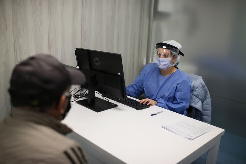 A doctor wearing protective gear talks to a patient inside a Zerenia clinic medical office, the first clinic specializing in medical marijuana treatments, in Bogota