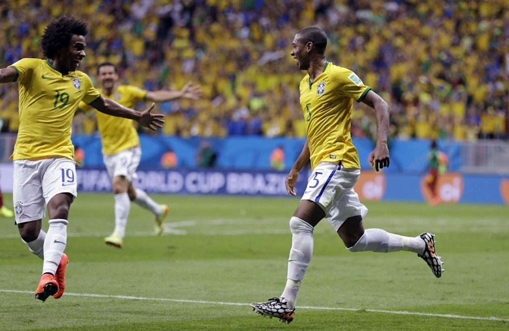 Brazil's Fernandinho, right, celebrates scoring his side's fourth goal during the group A World Cup soccer match between Cameroon and Brazil at the Estadio Nacional in Brasilia, Brazil, Monday, June 23, 2014