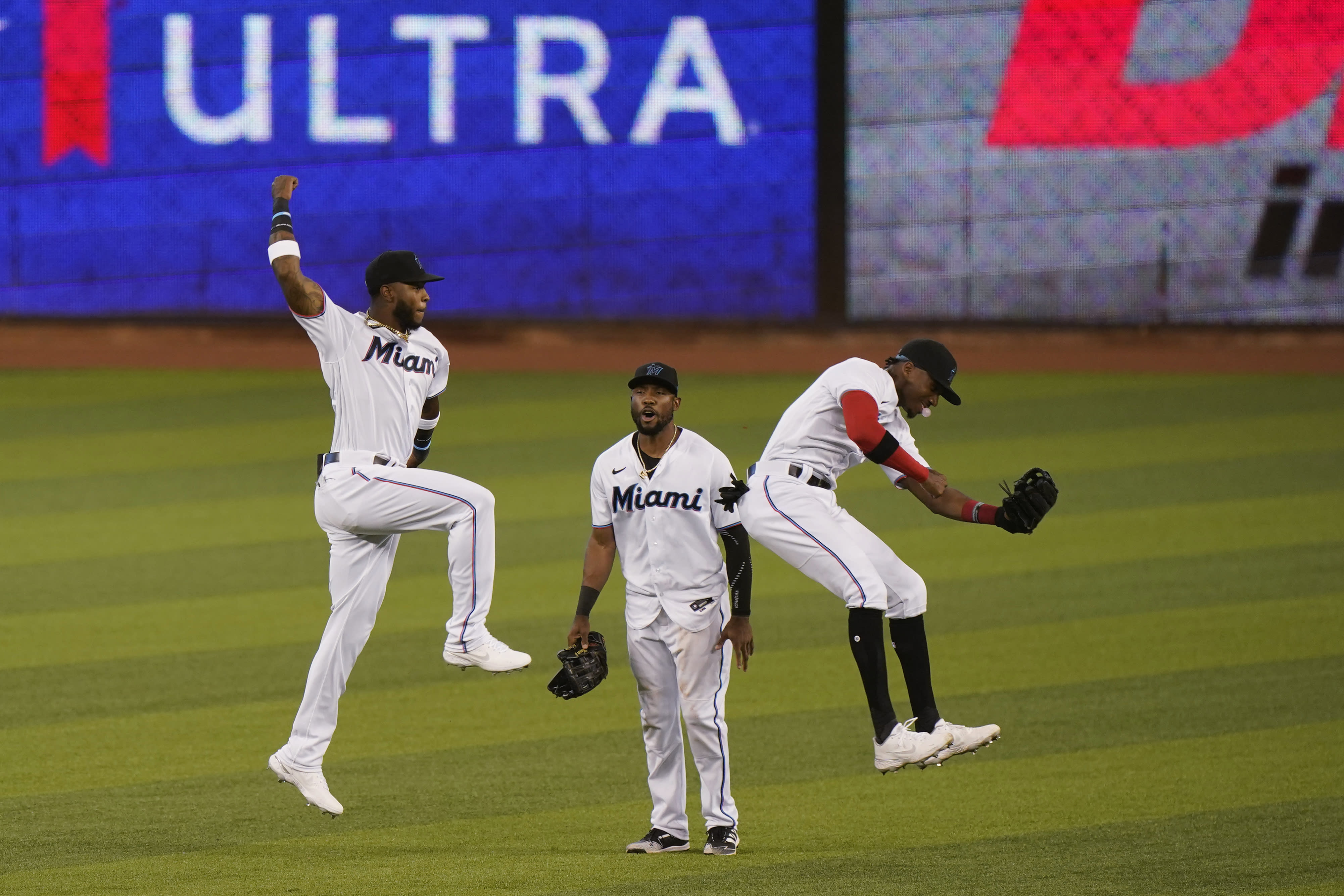 Miami Marlins' Starling Marte, center, watches as Monte Harrison, left, and Lewis Brinson leap to celebrate after they defeated the Philadelphia Phillies in the first game of a baseball doubleheader, Sunday, Sept. 13, 2020, in Miami. (AP Photo/Wilfredo Lee)