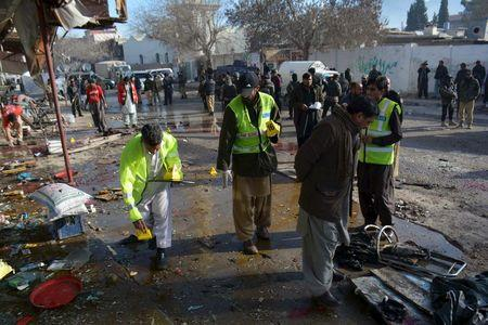 Crime scene investigators collect evidence from the site of a suicide bomb attack close to a polio eradication centre in Quetta, Pakistan, January 13, 2016. REUTERS/Stringer