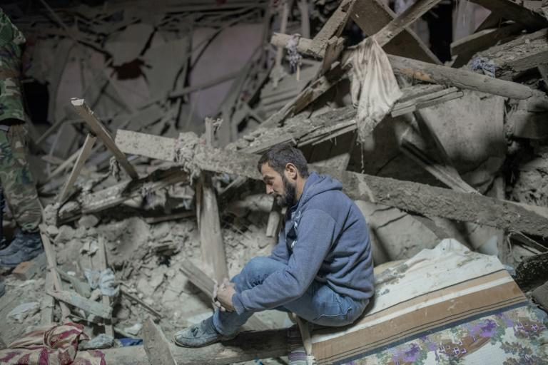A Ganja resident sits the rubble of building and waits for rescue teams to search for his relatives