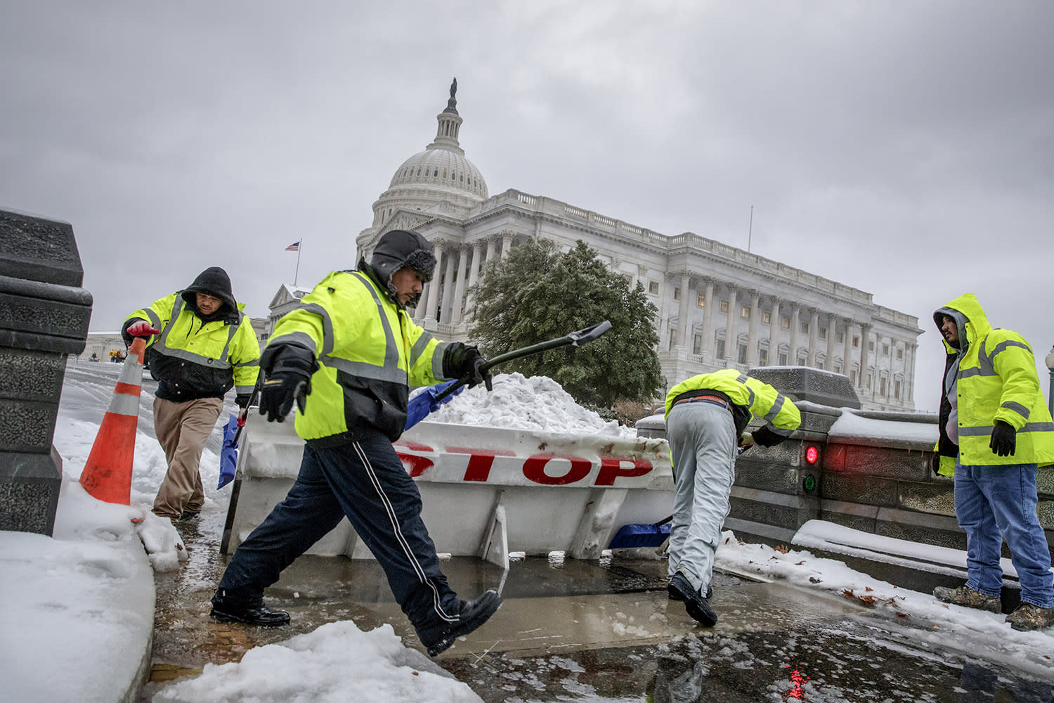 <p>Workmen clear snow from a security barricade on Capitol Hill in Washington, Tuesday, March, 14, 2017. A late-season storm is dumping a messy mix of snow, sleet and rain on the mid-Atlantic, complicating travel, knocking out power and closing schools and government offices around the region. (J. Scott Applewhite/AP) </p>