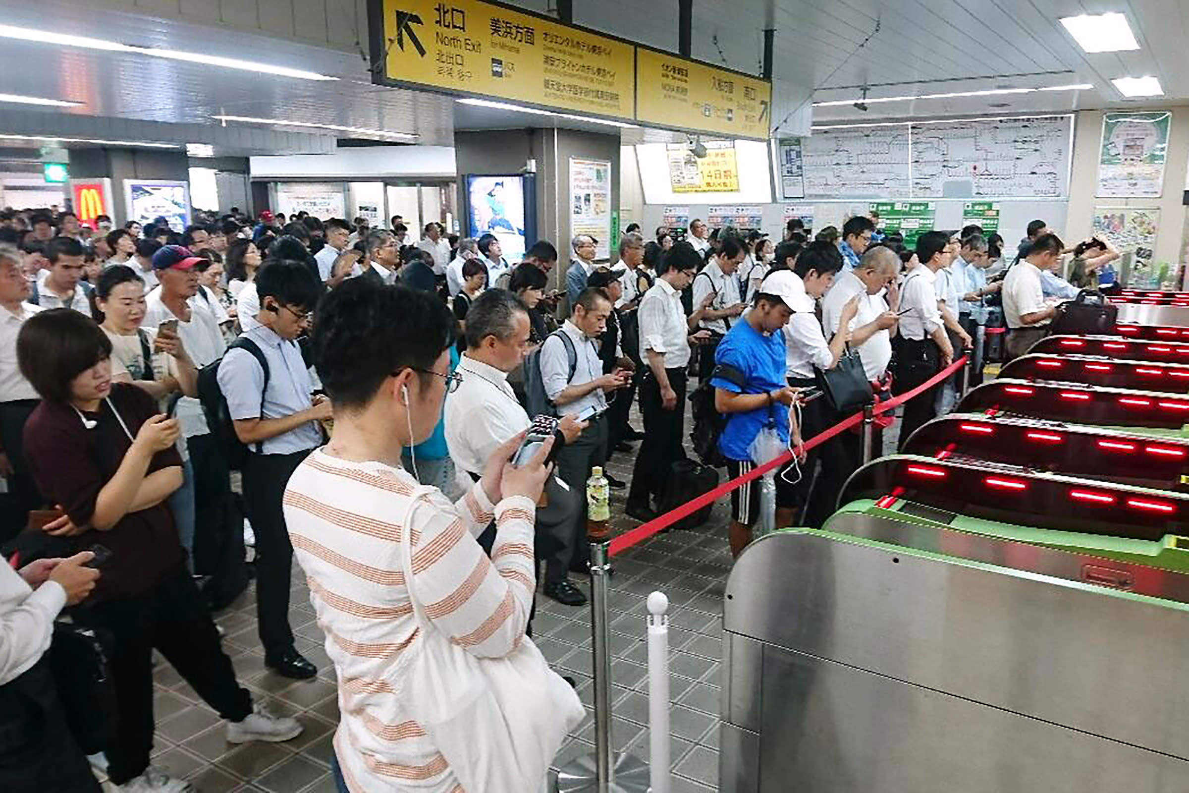 People wait for train operation to resume as it was suspended typhoon in Urayasu, east of Tokyo, Monday, Sept. 9, 2019.. (Kyodo News via AP)