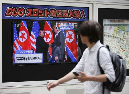 A passerby watches a TV broadcasting a news report on the summit between the U.S. and North Korea, in Tokyo, Japan, June 12, 2018. REUTERS/Issei Kato