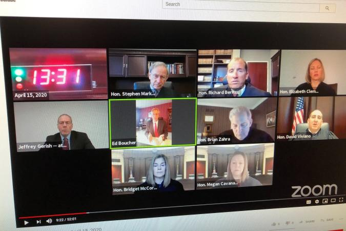 """In this photo taken of a computer screen Wednesday, April 15, 2020, shows the Michigan Supreme Court who broke new ground by hearing two cases via Zoom video conferencing. Justice David Viviano was the only judge in his regular seat in court. At one point more than 180 people were watching live on YouTube. Justice Richard Bernstein, perhaps the most loquacious member, had questions for the lawyers as time was winding down. """"Even on Zoom he finds a way"""" to run out the clock, Chief Justice Bridget McCormack joked. (AP Photo/Ed White)"""