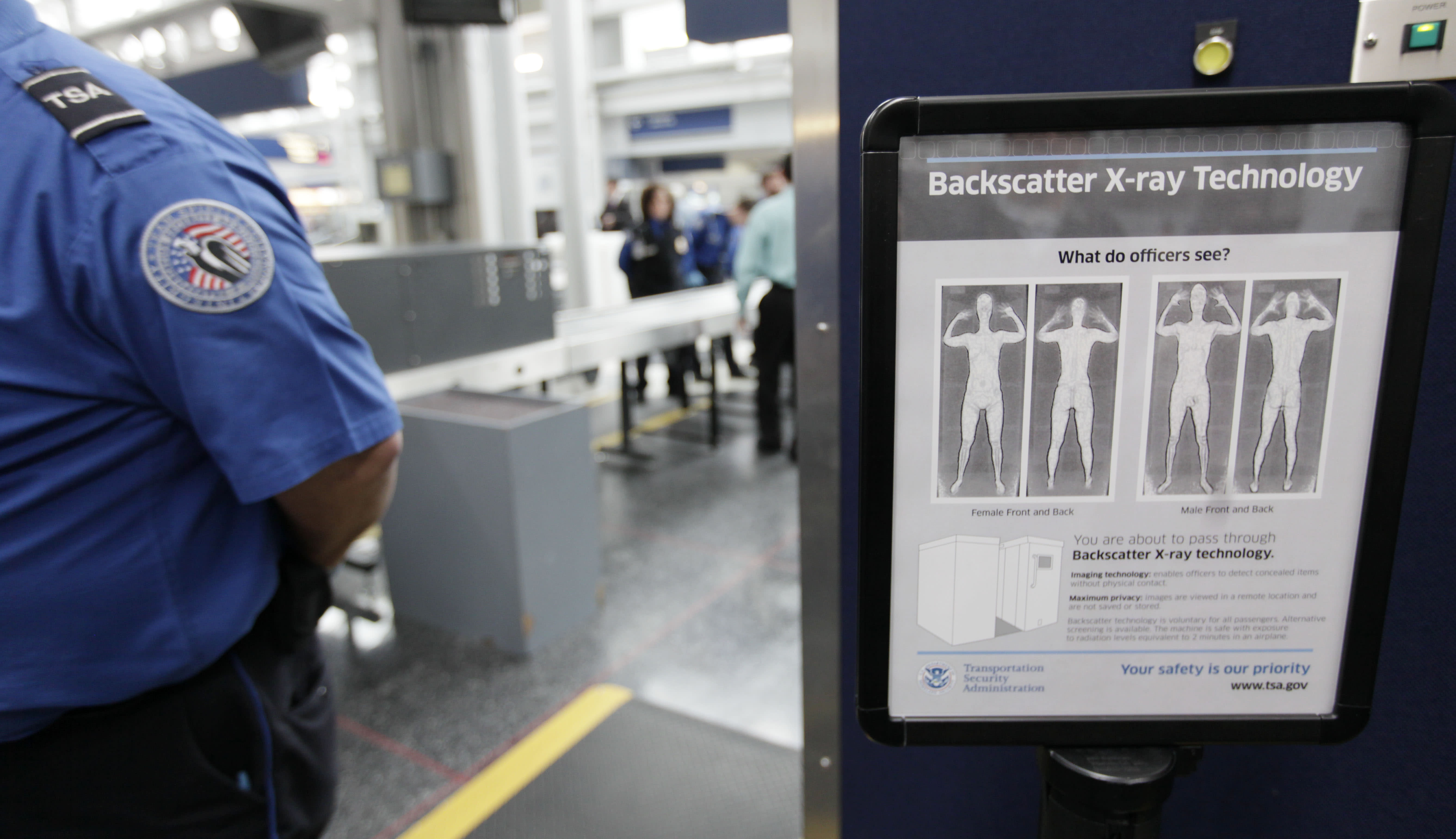FILE - In this March 15, 2010 file photo, a sign next to a body scanner describes what Transportation Security Administration officers see on their computer screens as volunteers go through the first full body X-rayscanner installed at O'Hare International Airport in Chicago. The Transportation Security Administration has been replacing the huge X-ray machines with smaller, millimeter wave body scanners at seven major U.S. airports. The new technology produces a cartoon-like outline rather than naked images of passengers produced by using X-rays. (AP Photo/M. Spencer Green, File)