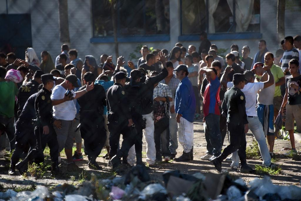 Guatemalan anti-riot policem guard a group of inmates after regaining the control of Canada maximum security prison in Escuintla department, 75 km south of Guatemala City on November 30, 2015 (AFP Photo/Johan Ordonez)