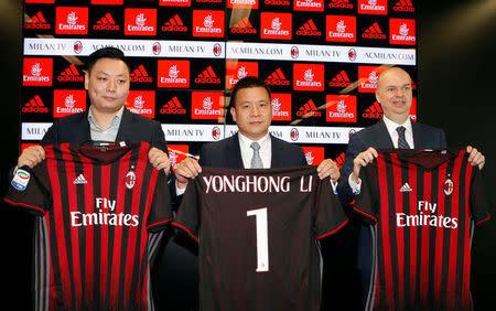 David Han Li (I), Yonghong Li (C) y Marco Fassone muestran una camiseta del AC Milan durante una conferencia de prensa en Milán, Italia.