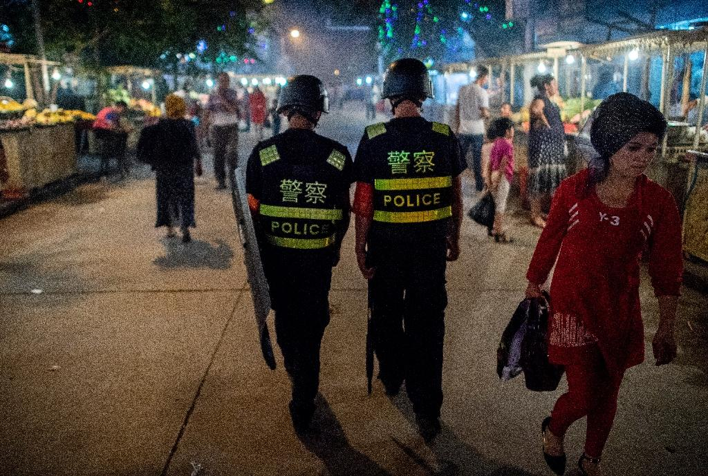 Police patrol a night food market near the Id Kah Mosque in Kashgar, in China's Xinjiang Uighur Autonomous Region, one day before the Eid al-Fitr holiday in June 2017