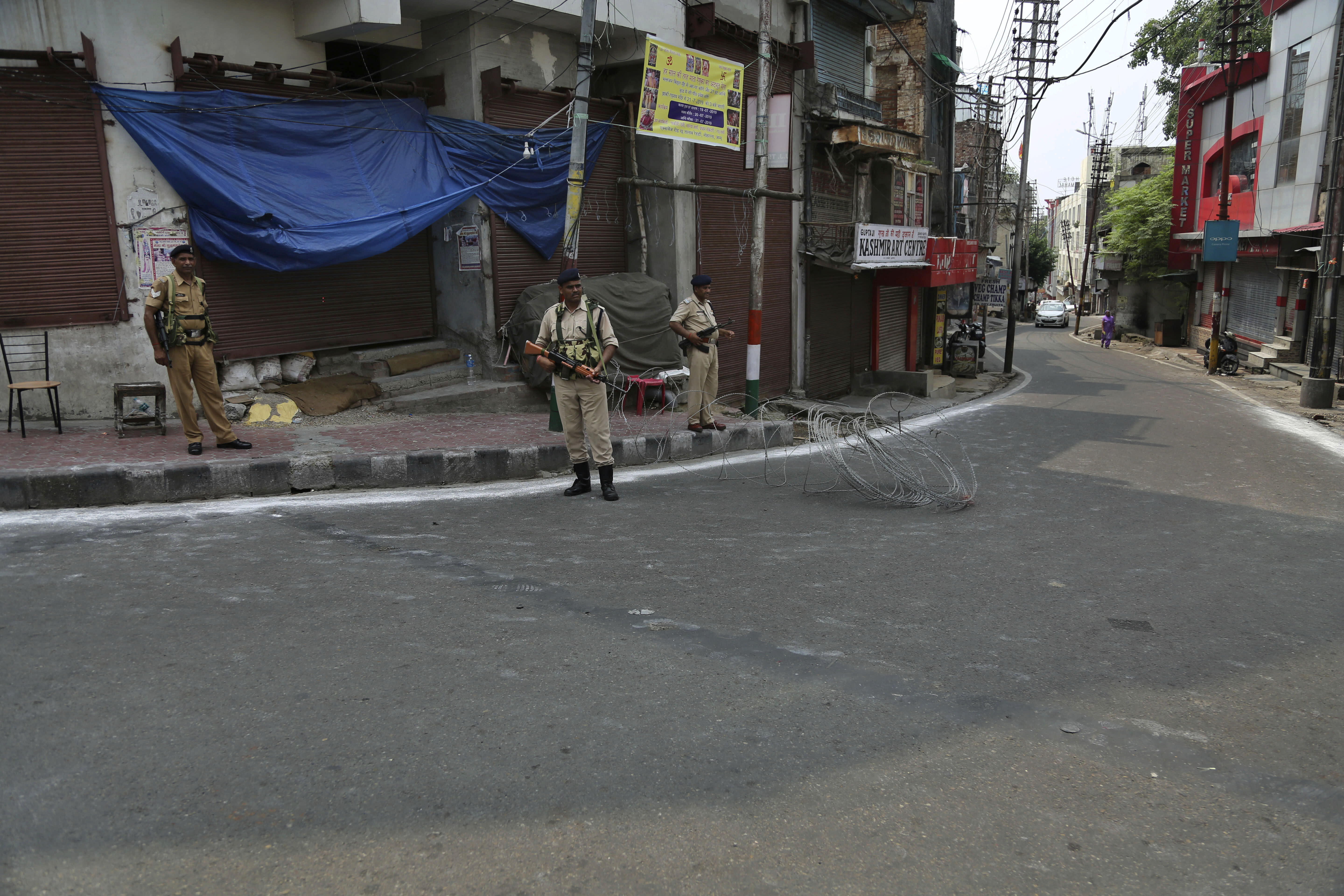 """Indian paramilitary soldiers gurad during security lockdown in Jammu, India, Tuesday, Aug.6, 2019. India's lower house of Parliament was set to ratify a bill Tuesday that would downgrade the governance of India-administered, Muslim-majority Kashmir amid an indefinite security lockdown in the disputed Himalayan region. The Hindu nationalist-led government of Prime Minister Narendra Modi moved the """"Jammu and Kashmir Reorganization Bill"""" for a vote by the Lok Sahba a day after the measure was introduced alongside a presidential order dissolving a constitutional provision that gave Kashmiris exclusive, hereditary rights. (AP Photo/Channi Anand)"""