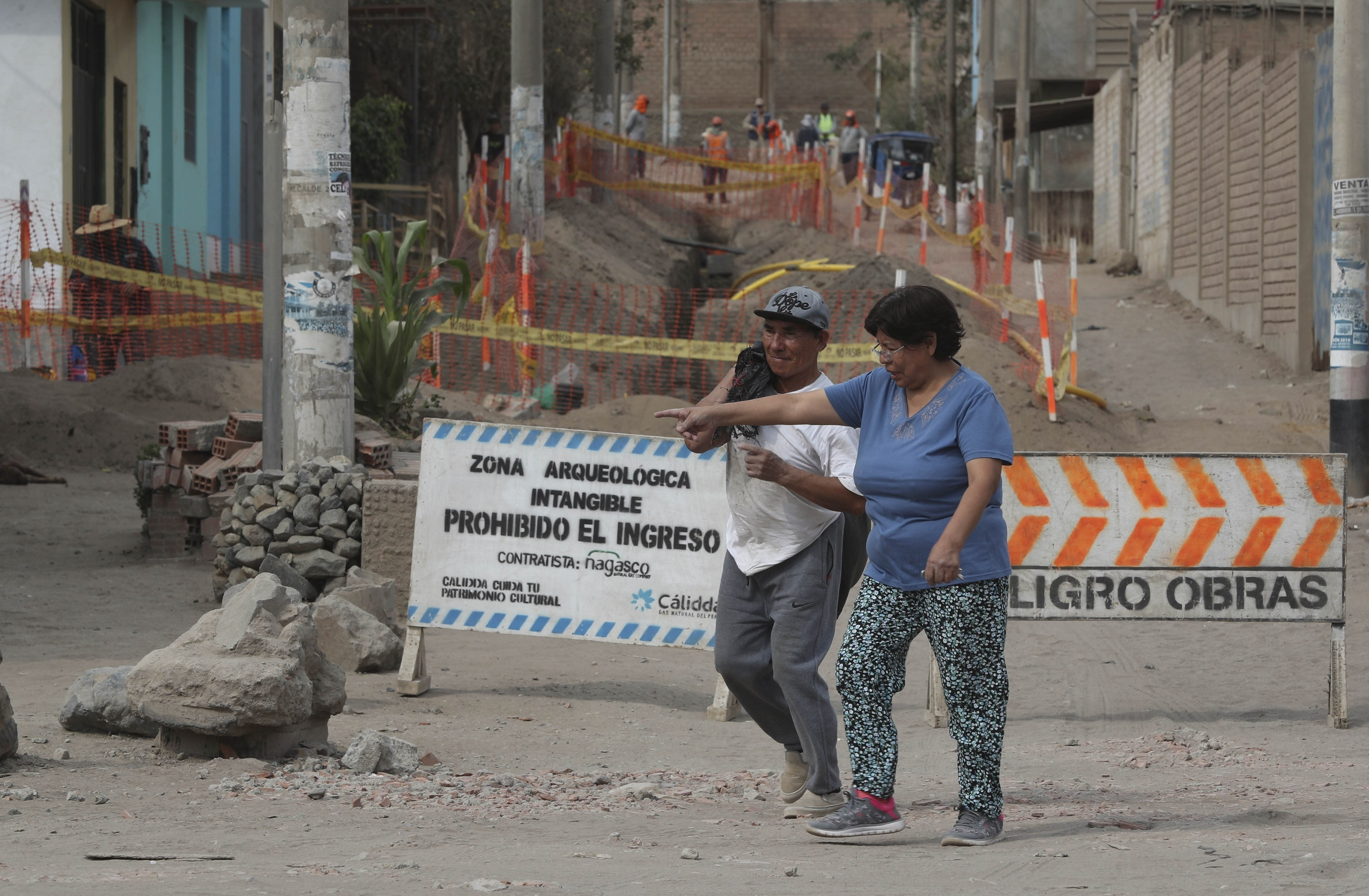 "In this Feb. 12, 2020 photo, residents walk past signs that read in Spanish ""Intangible archeological zone. Entrance prohibited,"" left, and ""Danger. Works."" where workers digging for a natural gas line ran into ancient bones and vessels from a previous Inca culture in the Puente Piedra neighborhood of Lima, Peru. About 300 archaeological finds, some 2,000 years old, have been reported over the past decade during the building of thousands of kilometers (miles) of natural gas pipelines in the capital. (AP Photo/Martin Mejia)"