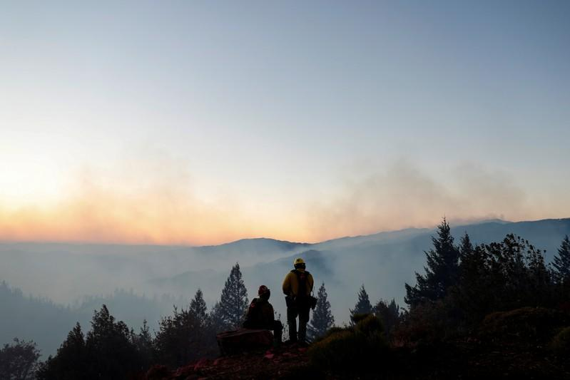 FILE PHOTO: Two firefighters watch from the top of a hill as the Kincade fire burns below in Calistoga, California