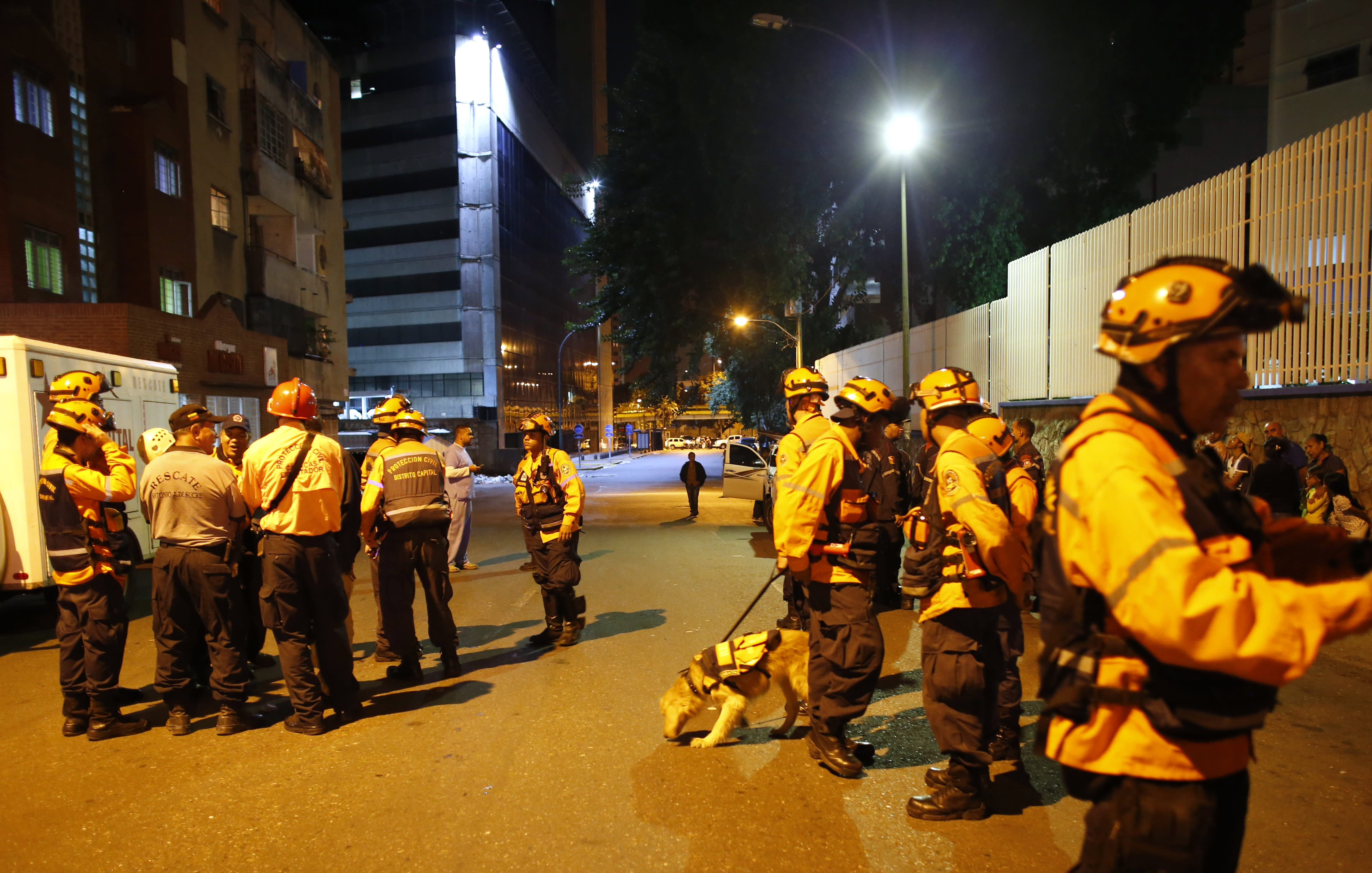 """Civil Protection workers patrol near the """"Tower of David"""" skyscraper, which suffered an inclination after a powerful earthquake shook eastern Venezuela, causing buildings to be evacuated in the capital of Caracas, Venezuela, Tuesday, Aug. 21, 2018. The quake was felt as far away as Colombia's capital and in the Venezuelan capital office workers evacuated buildings and people fled homes. (AP Photo/Ariana Cubillos)"""