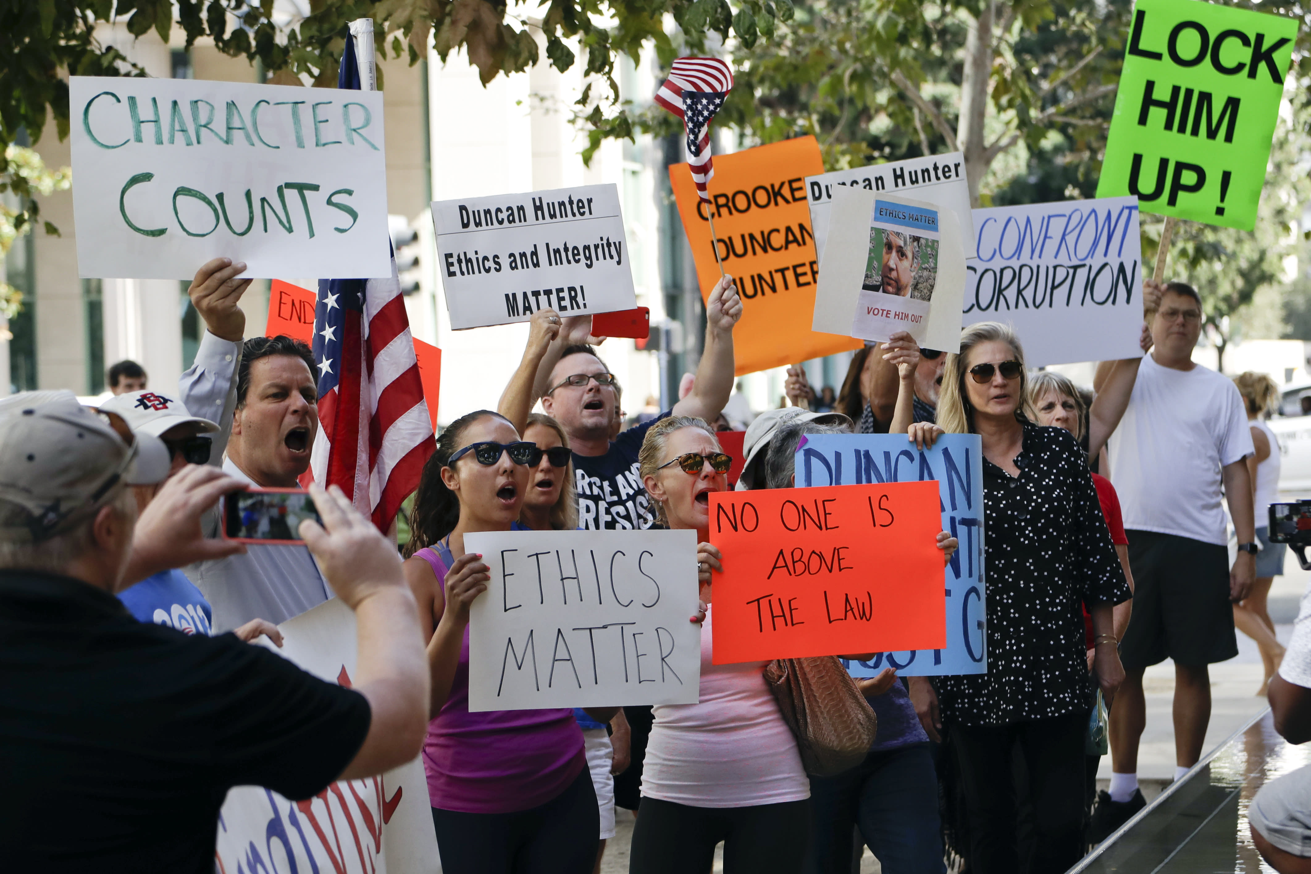 Protesters chant slogans as U.S. Rep. Duncan Hunter arrives for an arraignment hearing Thursday, Aug. 23, 2018, in San Diego. Hunter and his wife were indicted Tuesday on federal charges that they used more than $250,000 in campaign funds for personal expenses that ranged from groceries to golf trips and lied about it in federal filings, prosecutors said. (AP Photo/Gregory Bull)