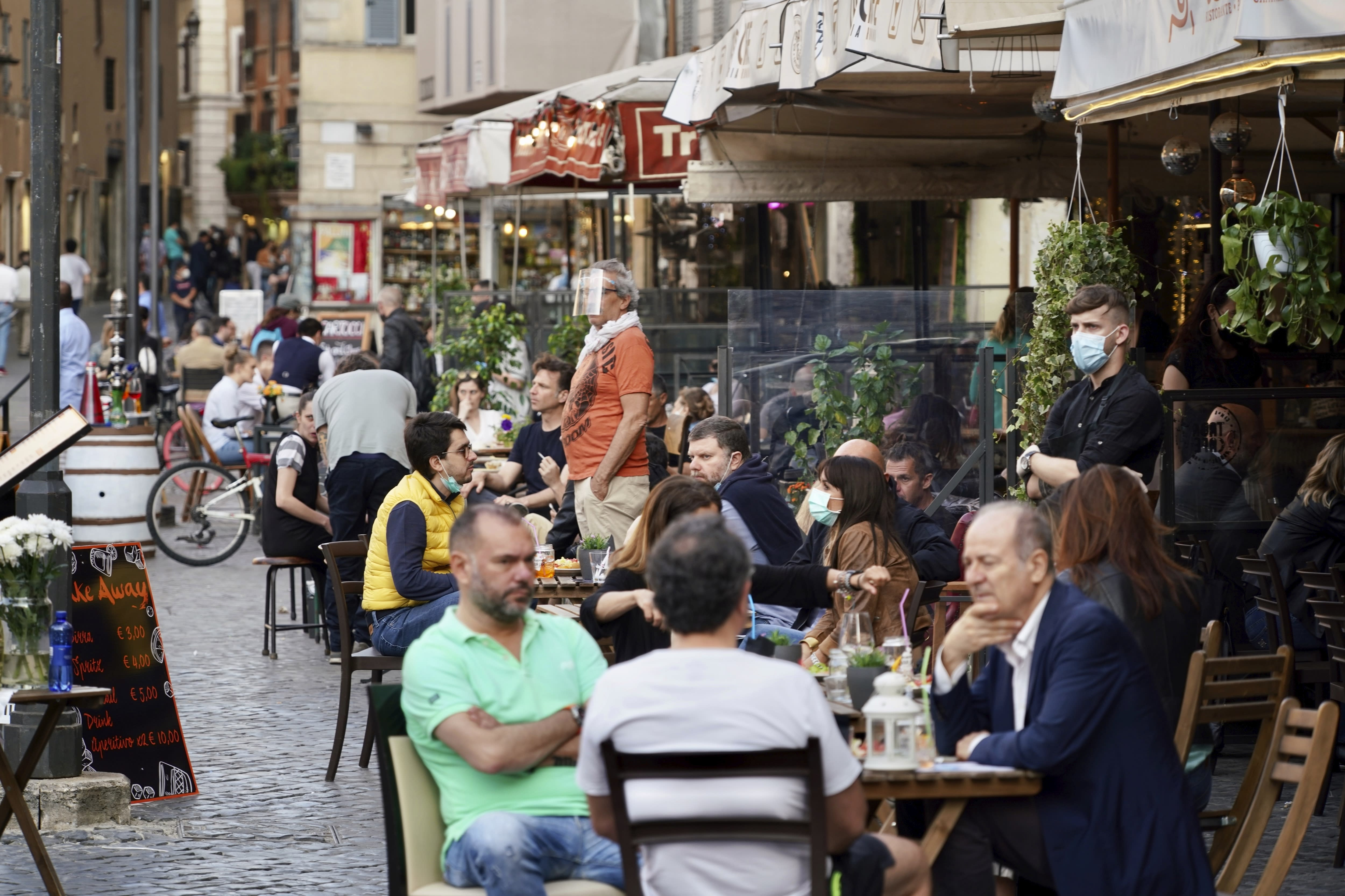 People sit at outdoor tables as they enjoy a drink on a Friday evening, in Rome's Campo dei Fiori square, Friday, May 22, 2020. Since Monday, Italians have regained freedoms, including being able to sit down at a cafe or restaurant, shop in all retail stores or attend church services such as Mass after a partial lifting of restriction measures aimed at containing the spread of COVID-19. (AP Photo/Andrew Medichini)