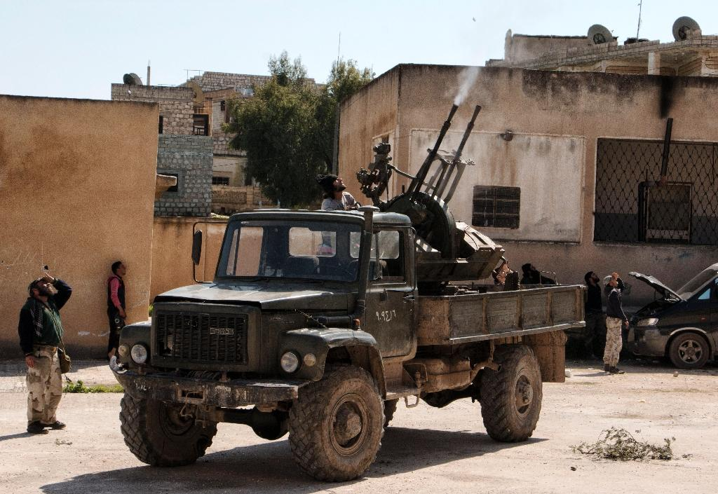 Rebel fighters fire an anti-aircraft machine gun mounted on a vehicle deploy in the northwestern Syrian city of Idlib on March 26, 2015