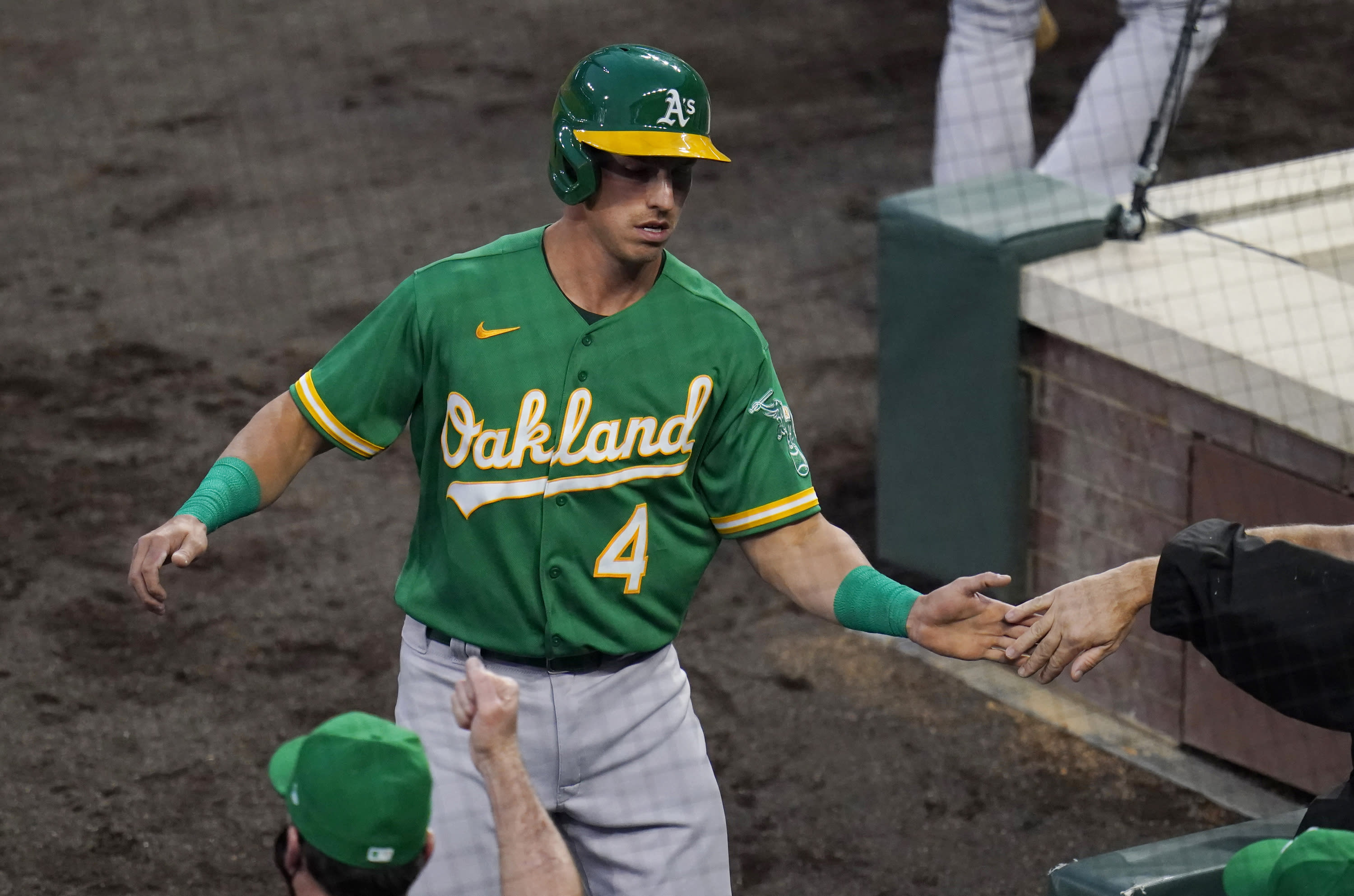 Oakland Athletics' Jake Lamb is congratulated after scoring against the Colorado Rockies during the second inning of a baseball game Tuesday, Sept. 15, 2020, in Denver. (AP Photo/Jack Dempsey)