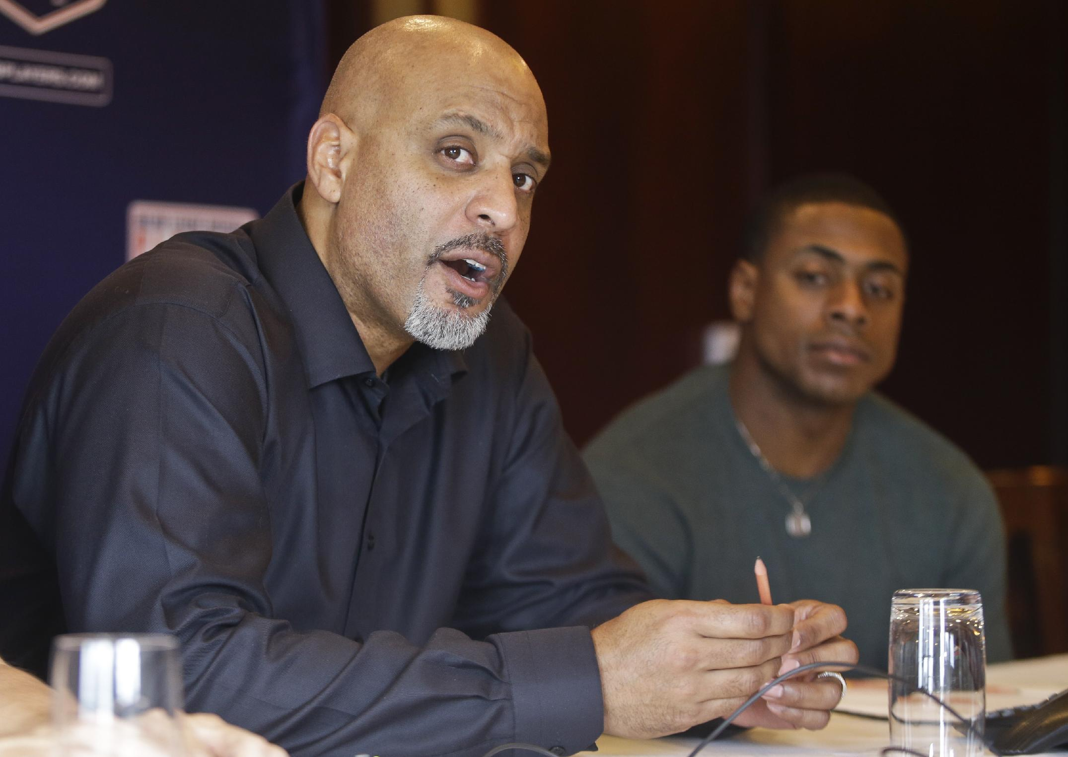 Tony Clark, left, the newly named Executive Director of the Major League Baseball Players Association, answers questions during a news conference at the organizations' annual meeting Tuesday, Dec. 3, 2013, in San Diego. Clark, who replaced the late Michael Weiner, is flanked by executive board member Curtis Granderson. (AP Photo/Lenny Ignelzi)