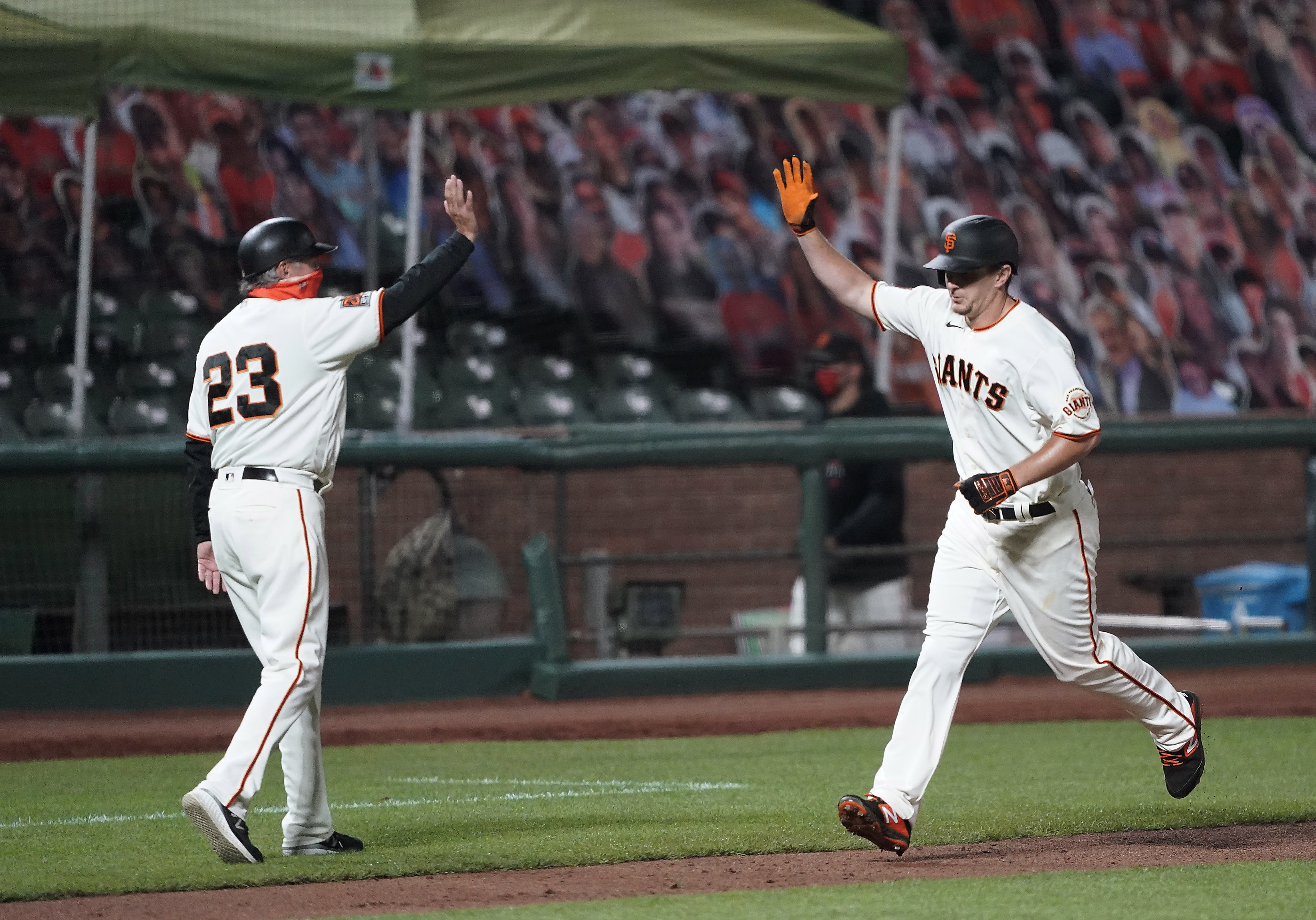 San Francisco Giants third base coach Ron Wotus, left, virtually high-fives Alex Dickerson, who runs the bases after hitting a solo home run against the Seattle Mariners during the third inning of a baseball game Tuesday, Sept. 8, 2020, in San Francisco. (AP Photo/Tony Avelar)