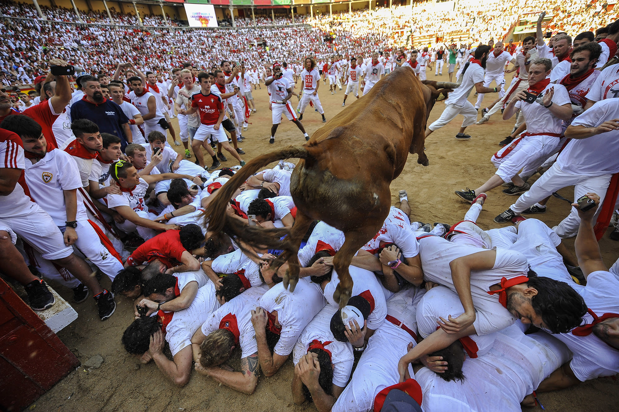 <p>A cow jumps over revelers during cow's festival at the end second running of the bulls at the San Fermin Festival, in Pamplona, norther Spain, Friday, July 8, 2016. (Photo: Alvaro Barrientos/AP) </p>