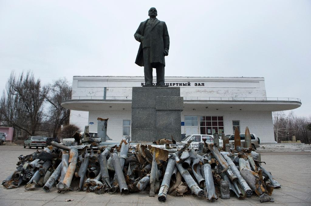 Debris of missiles, shells and rockets fired by Ukrainian forces on the frontline city of Pervomaisk are displayed at the foot of a statue of Lenin, on March 3, 2015 (AFP Photo/John Macdougall)