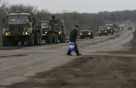 A local resident walks as a convoy of Ukrainian armed forces stand on the road near Artemivsk, eastern Ukraine, March 3, 2015. REUTERS/Gleb Garanich