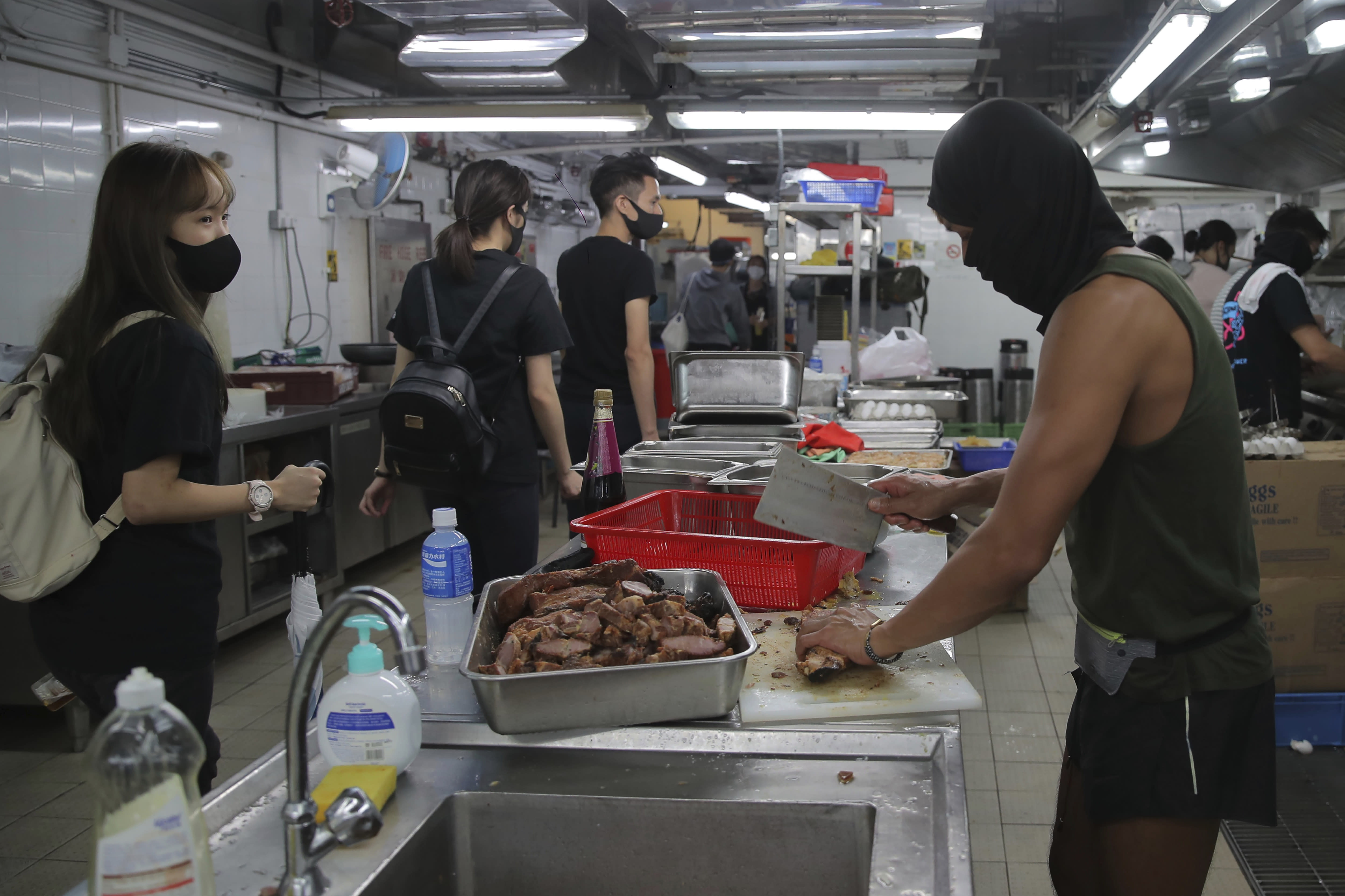 Protestors wear face masks as they cook meals for fellow protestors in a canteen at Hong Kong Polytechnic University in Hong Kong, Thursday, Nov. 14, 2019. Hong Kong residents endured traffic snarls and mass transit disruptions Thursday as protesters closed some main roads and rail networks while police skirmished with militant students at major universities. (AP Photo/Kin Cheung)