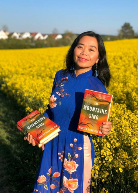 "Vietnamese author Nguyen Phan Que Mai holds copies of her novel ""The Mountains Sing"" (AFP Photo/Handout)"