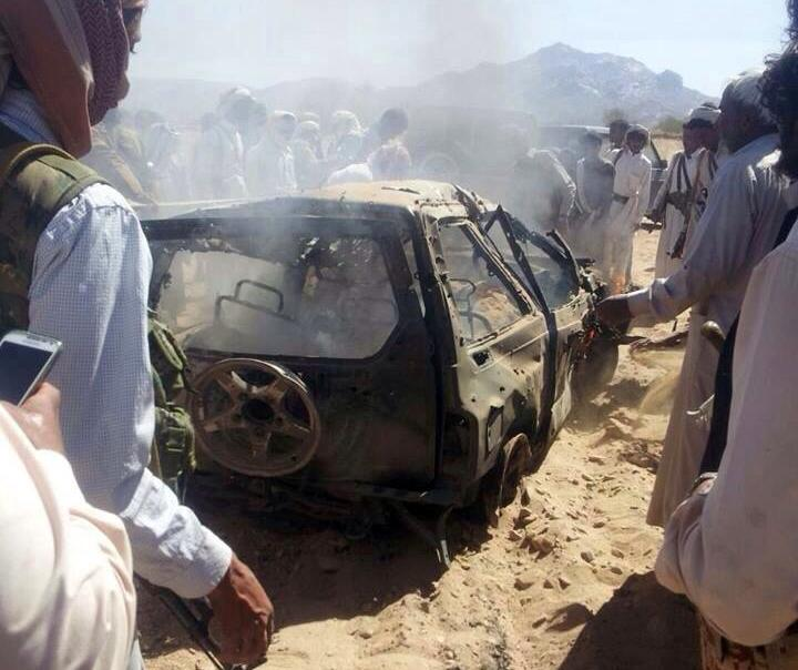 Yemenis gather around a burnt car after it was targeted by a drone strike killing three suspected al-Qaeda militants in January last year