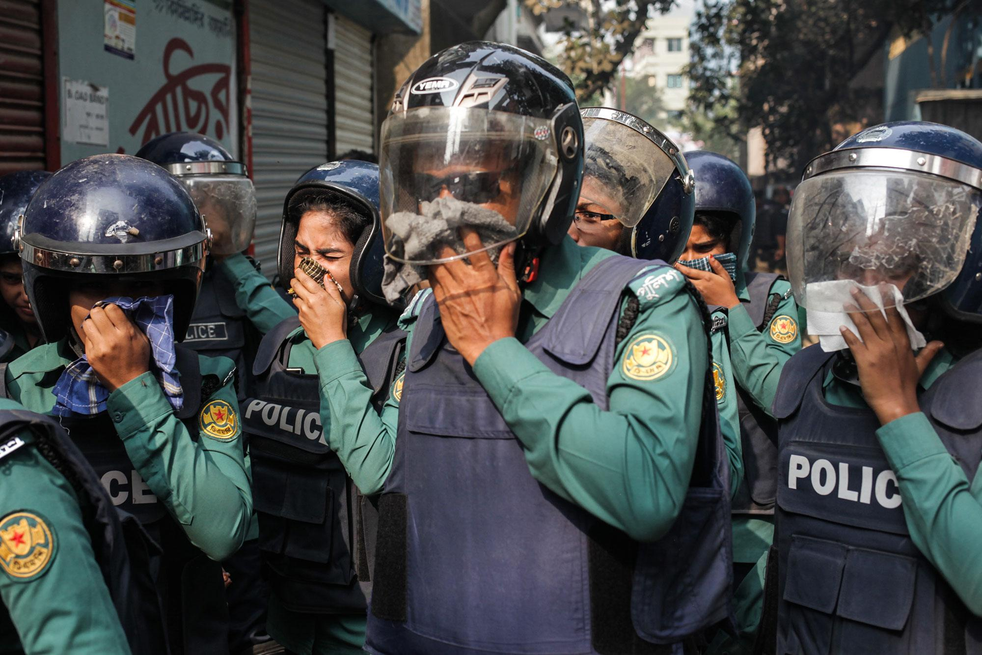 <p>Counter terrorism unit of Police hold their nose after the suicidal vest explosion by the militants at Ashkona in Dhaka, Bangladesh on Dec. 24, 2016. Two female militants along with two children surrendered to the cops, 1 female and a teen militant killed themselves during police raid by exploding suicidal vest outside their den while acting to surrender to the cops. (Photo: Anik Rahman/NurPhoto via Getty Images) </p>