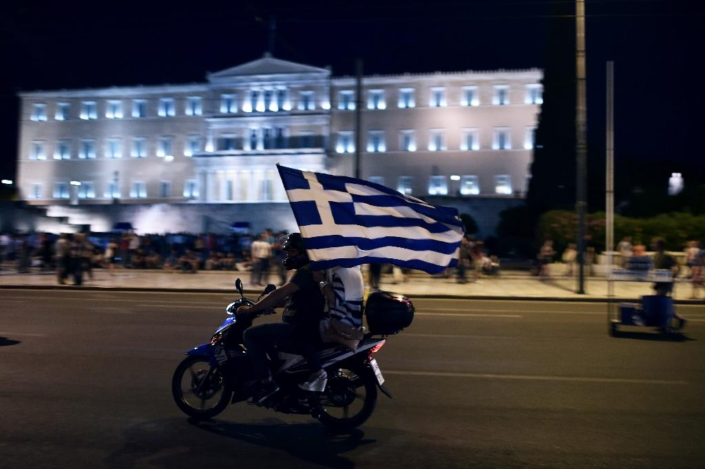 A motorcylist celebrates with a Greek flag in Athens on July 5, 2015 as the country voted to reject more austerity terms demanded by creditors in exchange for bailout funds (AFP Photo/Aris Messinis)