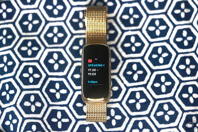 <p>Front view of the Fitbit Luxe with a gold mesh bracelet on a patterned blue and white background. Its screen shows a calendar notification for an event from 5:30pm to 7pm.</p>