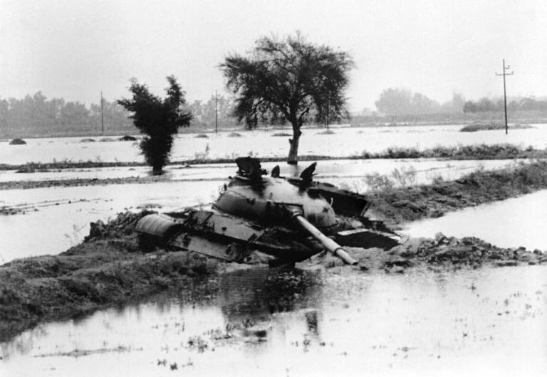Iraq's leader Saddam Hussein began the war with attacks on Iran including an aerial bombardment then sending in ground troops, with this December 8, 1980, photograph showing an Iraqi tank trapped in flood waters outside the Iranian town of Ahvaz