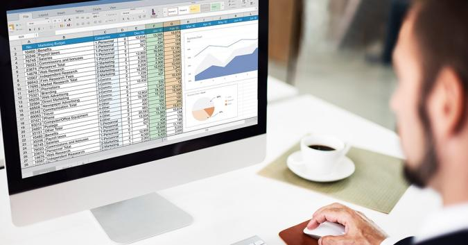 Over-the-shoulder stock image of a man working on a spreadsheet on an all-in-one desktop, with a cup of coffee nearby on the desk.