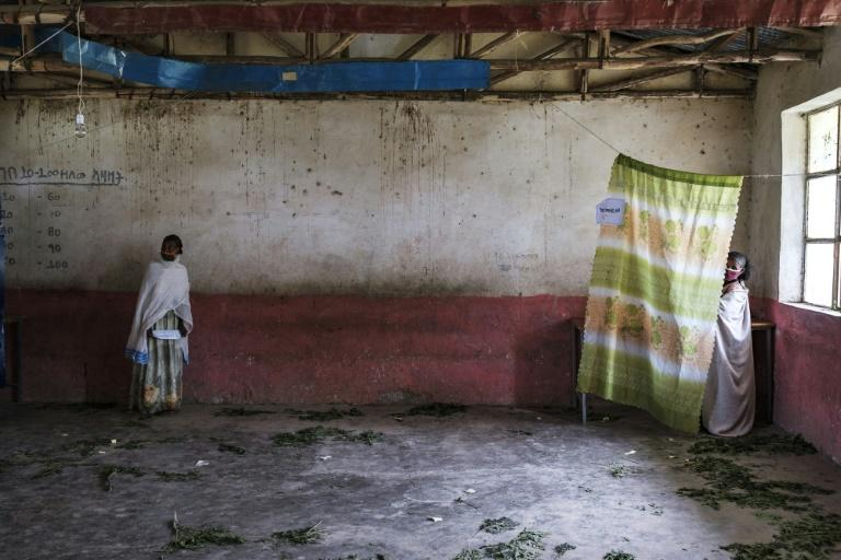 A woman stands in a voting booth as another waits in a polling station during Tigray's banned regional election