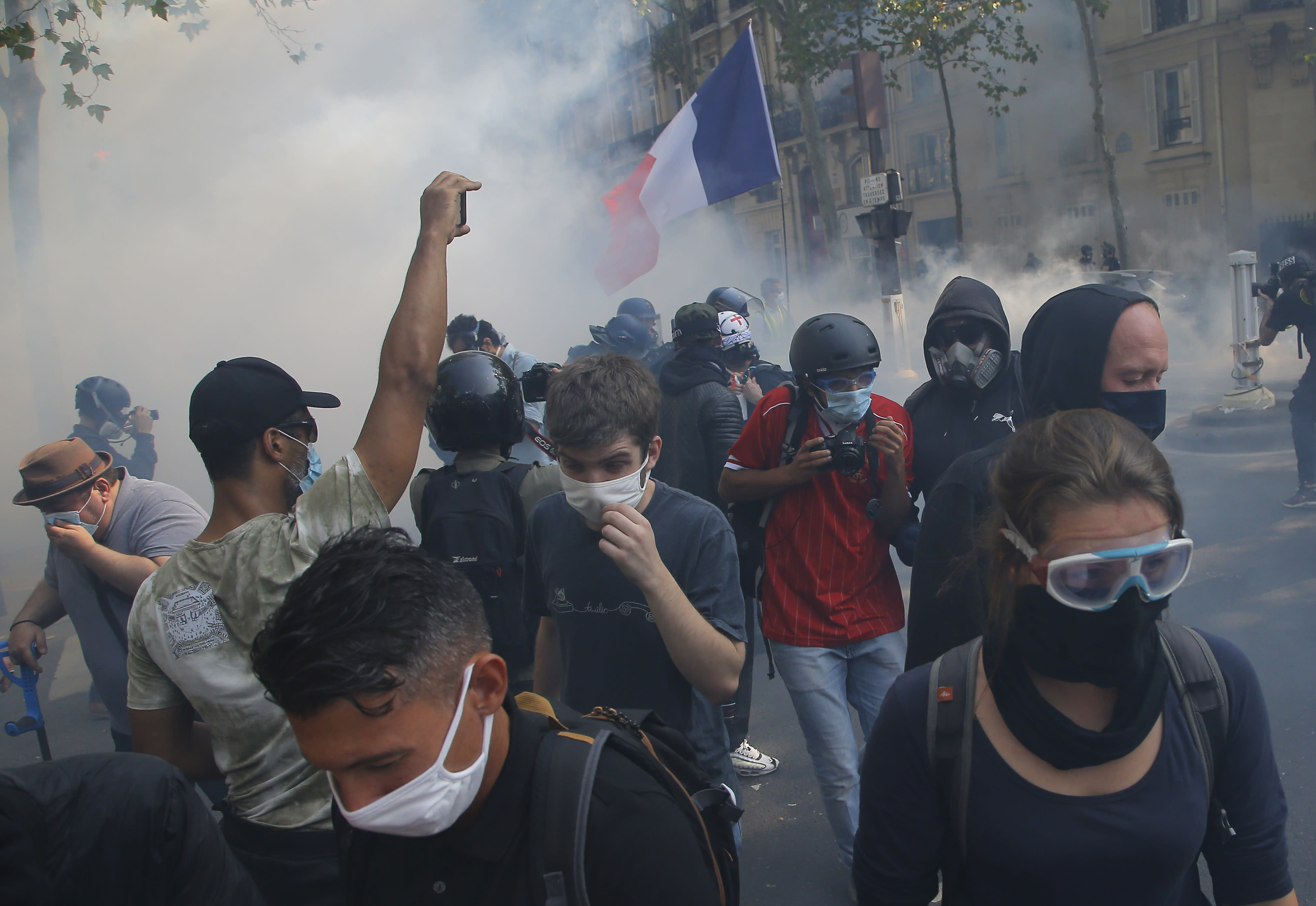 Yellow vest protesters escape tear gas fired by French police while wearing protective face masks as precaution against the conoravirus during a march in Paris, Saturday, Sept. 12, 2020. Activists relaunched France's yellow vest movement Saturday after the disruptive demonstrations against Emmanuel Macron's presidency and perceived elitism tapered off during the coronavirus pandemic.(AP Photo/Michel Euler)