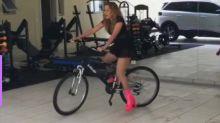 De salto alto, Joelma anda de bicicleta dentro de casa