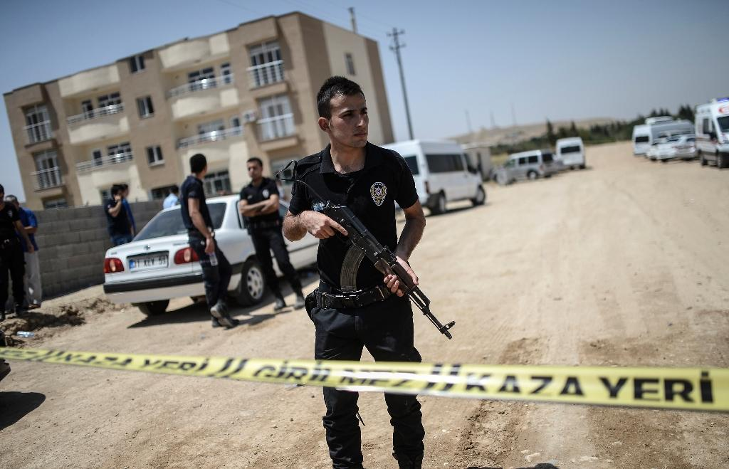 Turkish police stand near a building where two police officers were found shot dead at their home on July 22, 2015 in the Turkish town of Ceylanpinar (AFP Photo/Bulent Kilic)