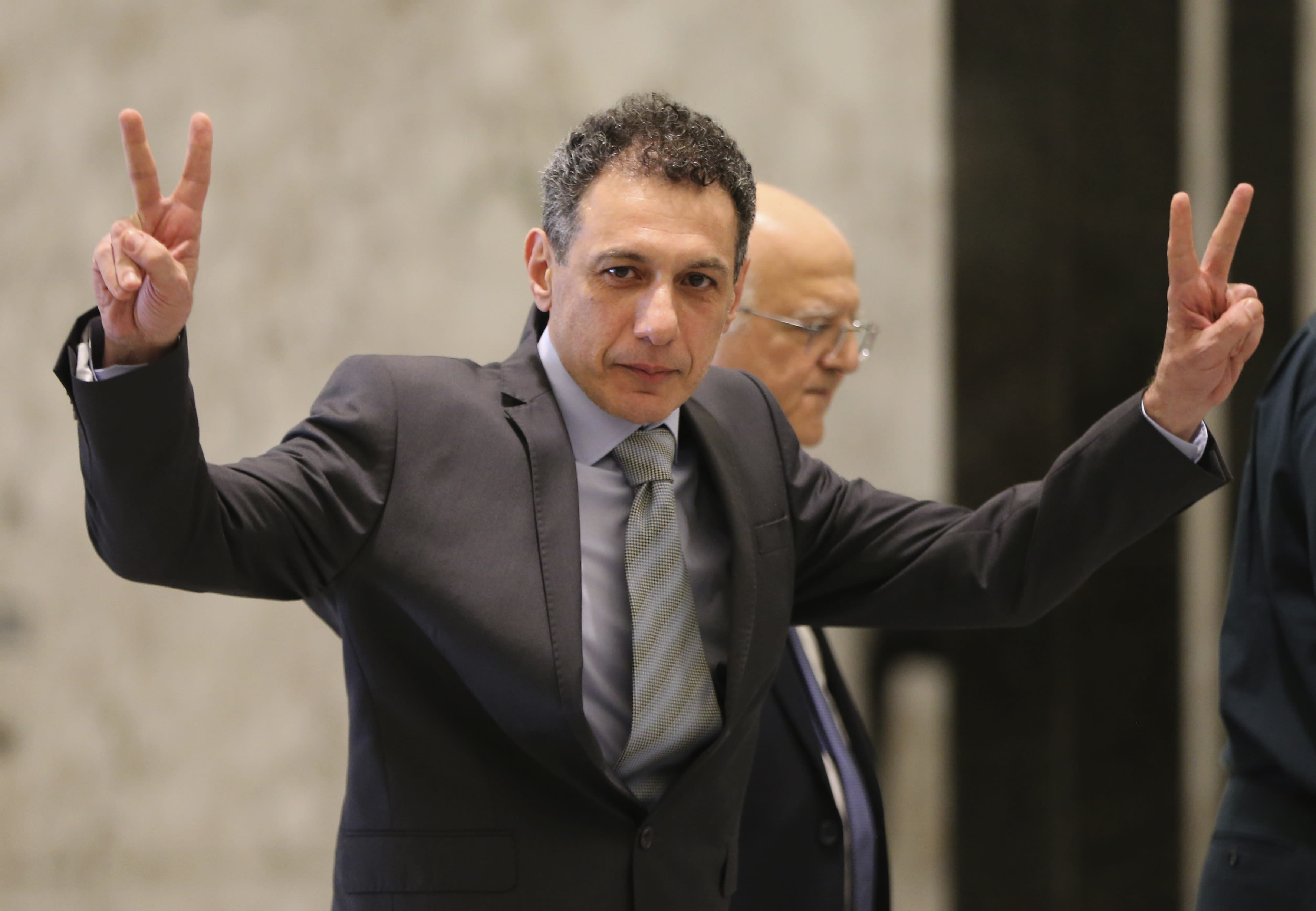 Nizar Zakka, a Lebanese citizen and U.S. permanent resident, who was released in Tehran after nearly four years in jail on charges of spying, flashes victory signs upon his arrival at the presidential palace, in Baabda, east of Beirut, Tuesday, June 11, 2019. Zakka a Lebanese businessman was allowed to fly to Lebanon, a development that comes amid heightened tensions between Iran and the U.S. after President Donald Trump withdrew America from Tehran's nuclear deal with world powers. (AP Photo/Hussein Malla)