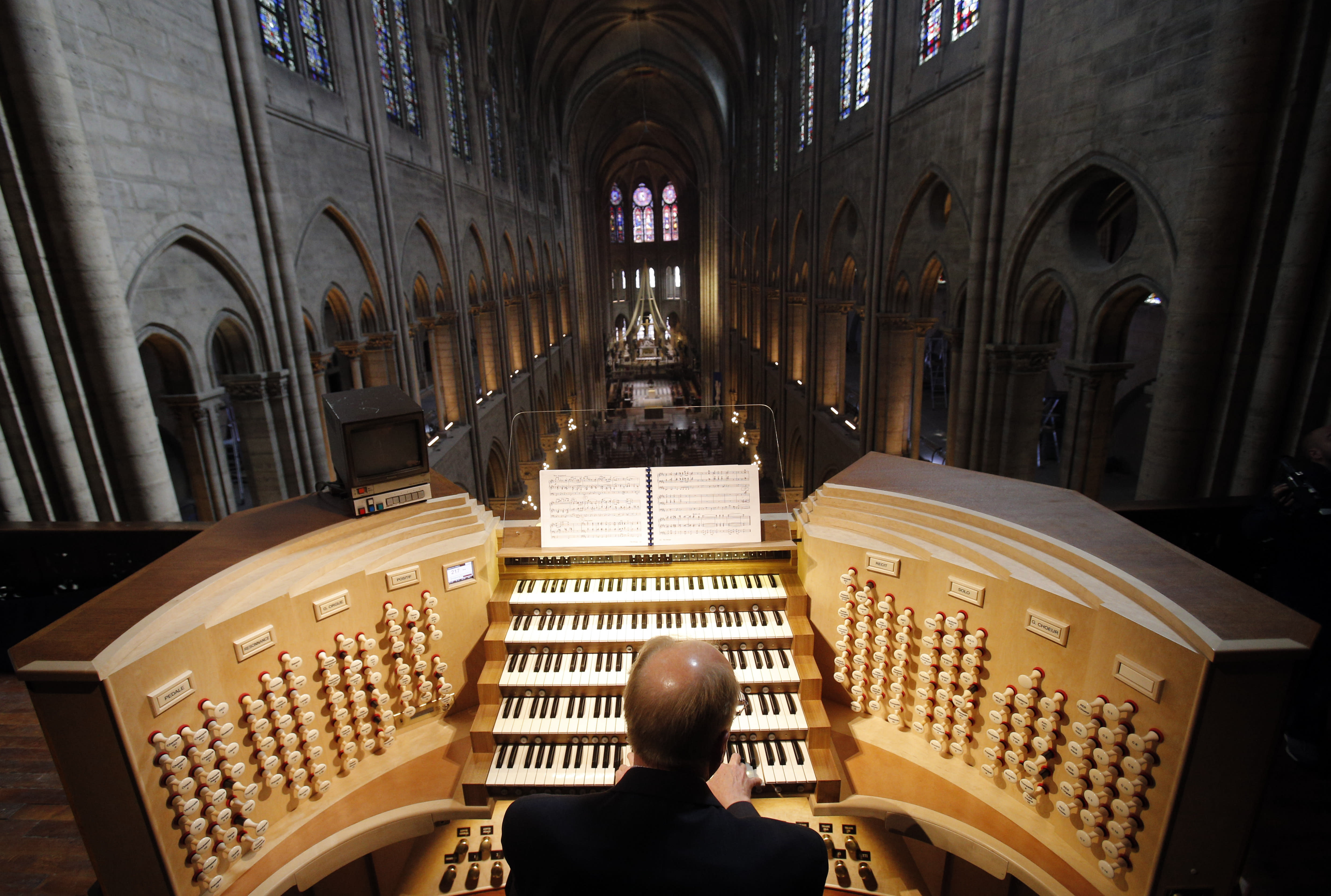 FILE - In this Thursday, May 2, 2013 file photo, Philippe Lefebvre, 64, plays the organ at Notre Dame cathedral in Paris. (AP Photo/Christophe Ena, file)
